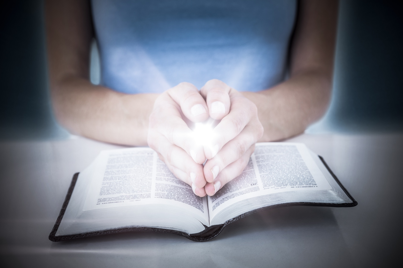 Composite image of woman praying while reading bible